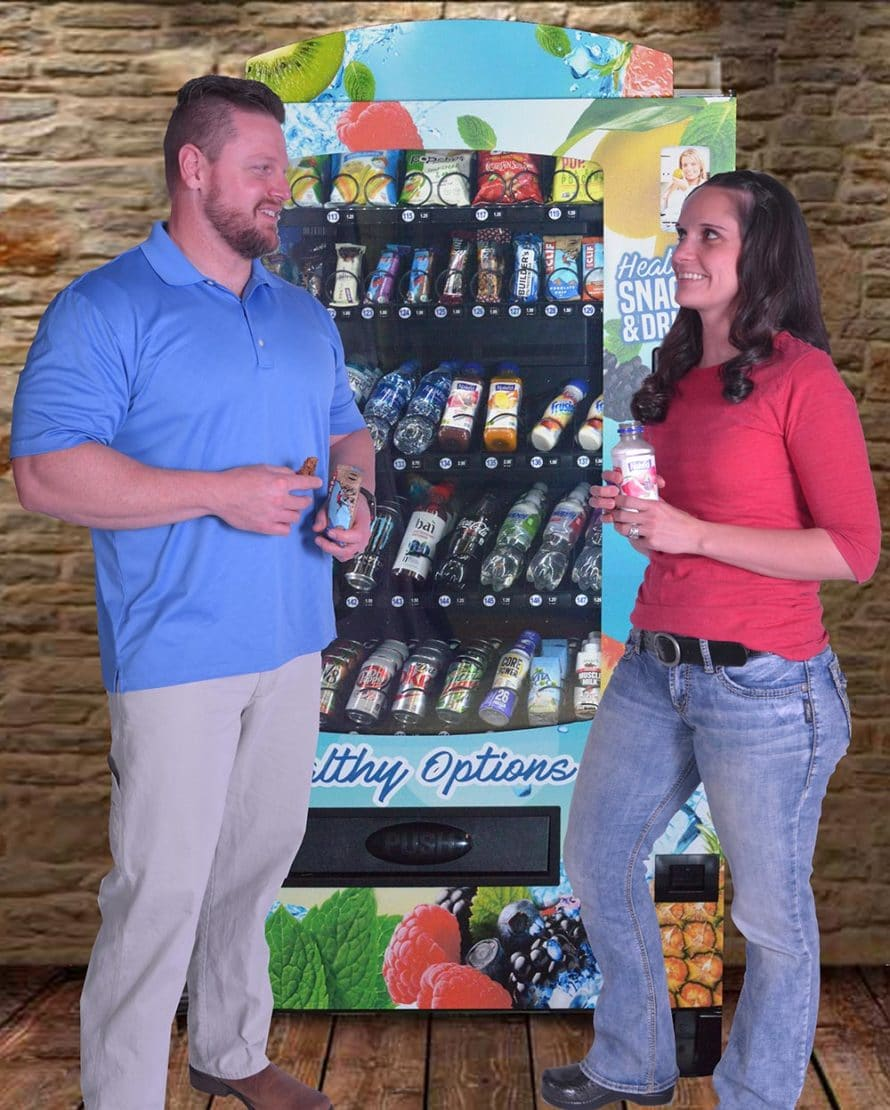 A man and woman standing in front of a new vending machine.
